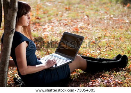 Young business woman using notebook mobile computer at city park. Working student - stock photo