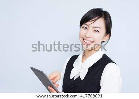 Young business woman using tablet computer against blue background - stock photo