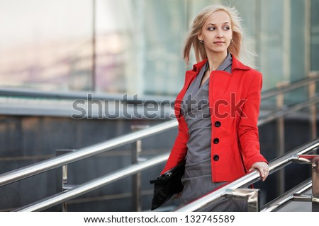 Young business woman walking on the city street - stock photo