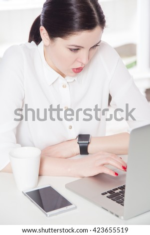 Young business woman wearing smartwatch using laptop computer. Beautiful assistant with dark hair, blue eyes working on laptop in the light white office. looking at display and working serious.