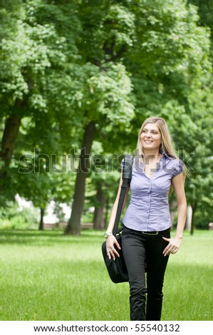 Young business woman wit laptob bag walking outdoors in park
