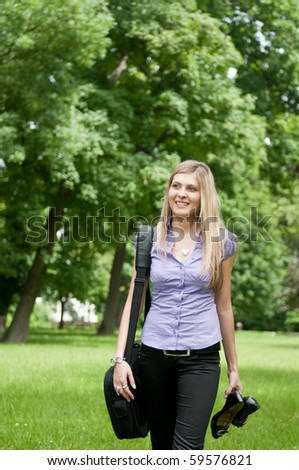 Young business woman wit laptob bag walking outdoors in park and holding shoes - stock photo