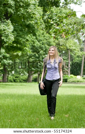 Young business woman wit laptop bag walking outdoors in park - stock photo