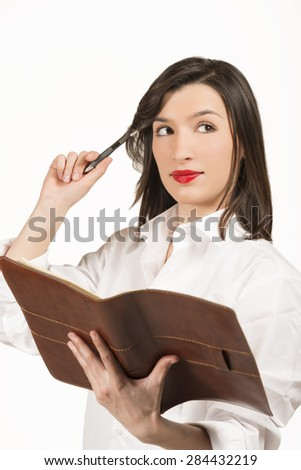 Young business woman with agenda. Thoughtful well dressed businesswoman checking her agenda, studio shot on white background