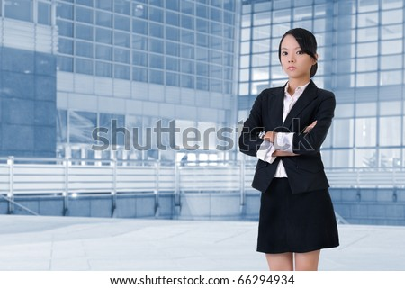 Young business woman with cool and confident expression standing in front of office. - stock photo