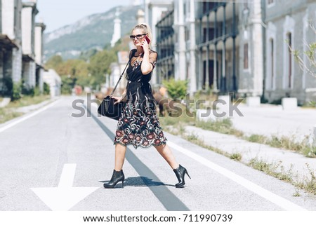 Young business woman with handbag running to catch the plane or train. Elegant trendy clothing. Hurrying to work concept.