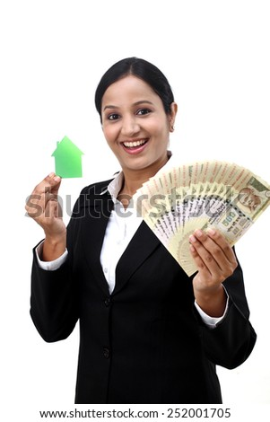 Young business woman with house model and Indian rupee notes in hands - stock photo