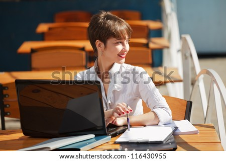 Young business woman with laptop at a sidewalk cafe - stock photo