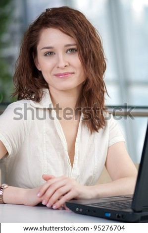 Young business woman with laptop at cafe - stock photo