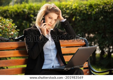 Young business woman with laptop calling on the cell phone  - stock photo