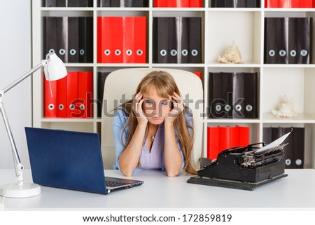 Young business woman  with notebook and old typewriter sits on workplace in the office. Progressing of technology. - stock photo