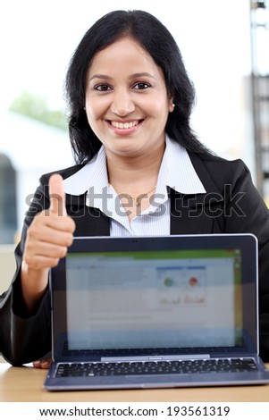 Young business woman with thumbs up gesture and showing tablet computer