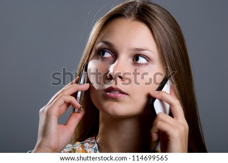 Young business woman with two mobile phones in talks. Isolated over gray background - stock photo