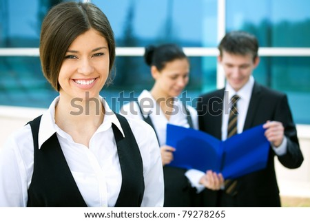 Young business woman with two of her co-workers on background  modern office building - stock photo