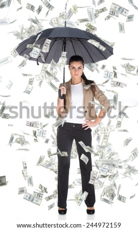 Young business woman with umbrella and money banknotes flying in air on the white background. - stock photo