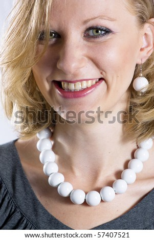 Young business woman with white necklace is smiling - stock photo