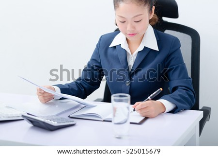 Young business woman working at desk in office.