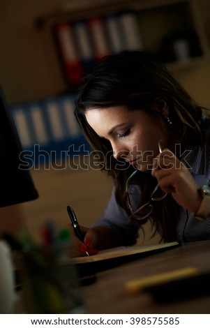 Young business woman working late in office. - stock photo