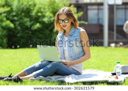 Young business woman working on laptop computer during picnic on green meadows outdoors.