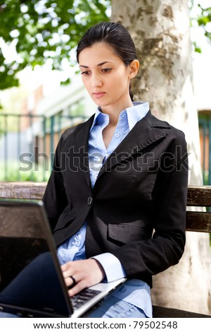 young business woman working on laptop in park - stock photo