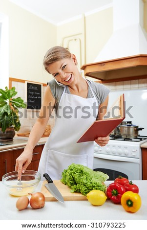 Young business woman working on phone and preparing meal with recipe book. Concept of diet and healthy nutrition.