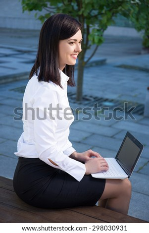 young business woman working with laptop in city park - stock photo