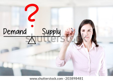 Young business woman writing demand and supply compare on balance bar. Office background. - stock photo