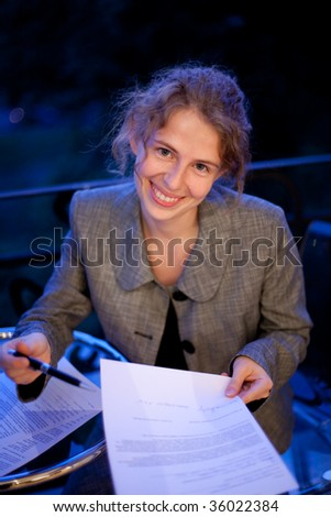 young business woman writing on a contract, at night - stock photo