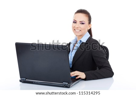 Young business woman writing on a laptop and looking at the camera with a big smile on her face. on white background - stock photo