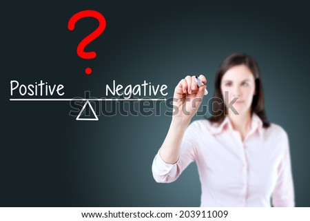Young business woman writing positive and negative compare on balance bar. Blue background. - stock photo