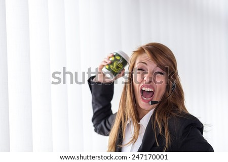 Young business woman yelling on the headphones during a phone call, throwing coffee - stock photo