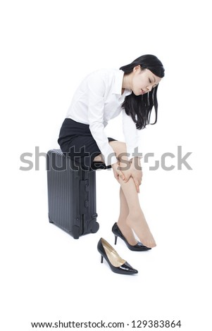 young business women massaging tired legs, isolated on white background
