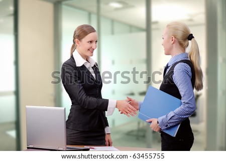 Young business women shaking hands over meeting at office - stock photo