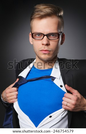 Young businessman acting like a super hero and tearing his shirt, isolated on gray background - stock photo