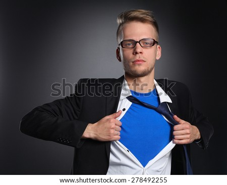 Young businessman acting like a super hero and tearing his shirt, isolated on gray background