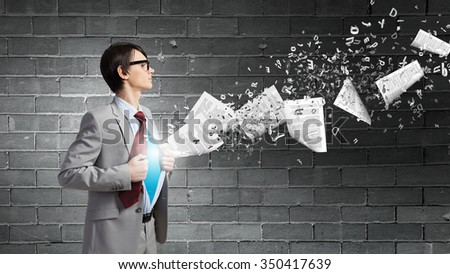 Young businessman acting like super hero and tearing his shirt off - stock photo