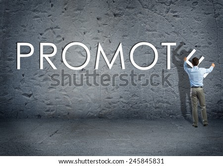 young businessman adds promote word on concrete wall - stock photo