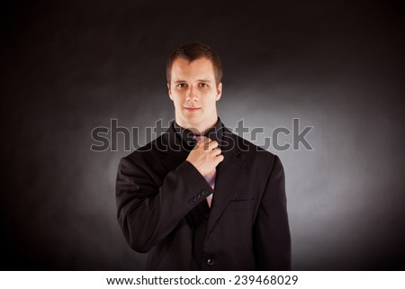 young businessman adjusting necktie - stock photo
