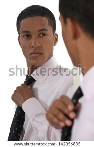 Young businessman adjusting tie before interview - stock photo