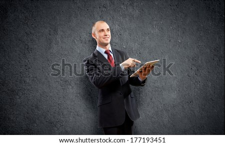 Young businessman against grey background using tablet pc