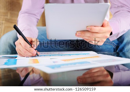Young businessman analyzing charts. Low angle view - stock photo