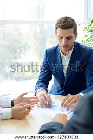 Young Businessman Analyzing Financial Results with Partners in the Modern Office. Team Work Concept
