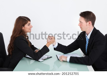 Young businessman and businesswoman arm wrestling on desk in office - stock photo