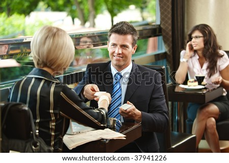 Young businessman and businesswoman having a meeting in cafe, exchanging business cards. - stock photo