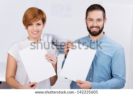 Young businessman and businesswoman holding blank papers while standing in office - stock photo