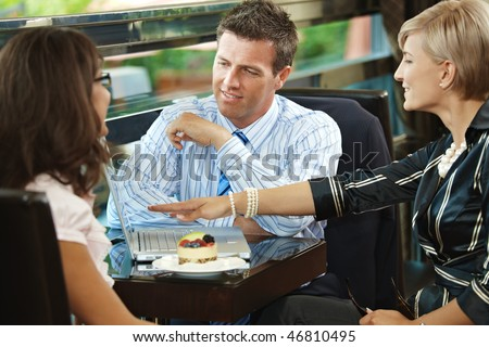 Young businessman and businesswomen having a meeting in cafe.