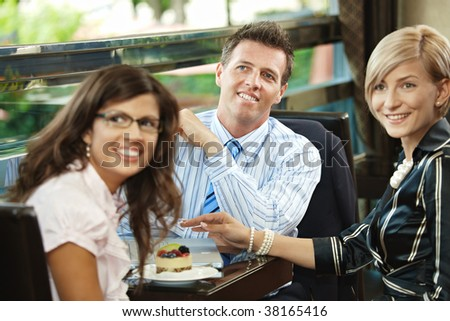 Young businessman and businesswomen having a meeting in cafe, smiling and greeting somebody. - stock photo