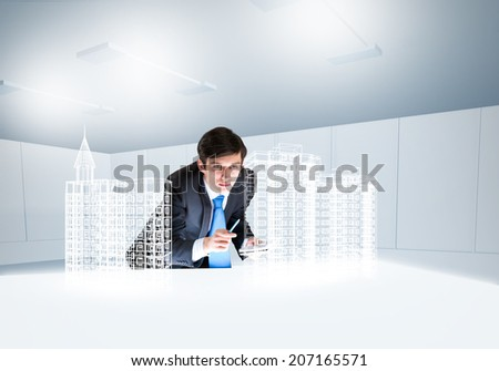 Young businessman and digital model of construction project - stock photo