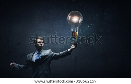 Young businessman and glass glowing light bulb - stock photo