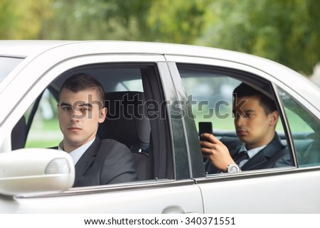 Young businessman and his driver in a car